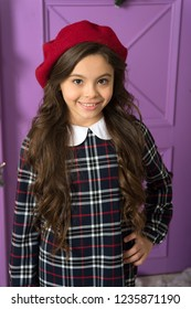 French style beret hat. How wear beret like fashion girl. Kid little girl with long hair posing in hat and checkered dress violet background. Fashionable beret hat for female. Beret style inspiration.