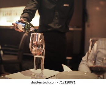At a french style dining room, Pouring Red Wine by waitress attractive concept