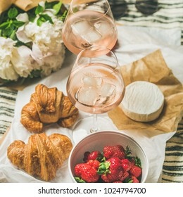 French style romantic summer picnic . Flat-lay of glasses with rose wine, fresh strawberries, croissants, brie cheese, hat, sunglasses, peony flowers, square crop. Outdoor gathering concept