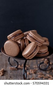 French tasty chocolate macaroons or macarons on dark brown wooden background - Shutterstock ID 570594331