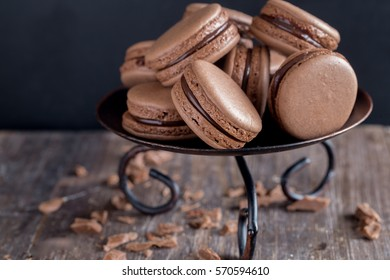 French tasty chocolate macaroons or macarons on dark brown wooden background - Shutterstock ID 570594610