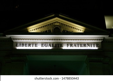 French text: Liberté, égalité, fraternité. English translation: Freedom, equality, fraternity. Inscription on the pediment of a monument at night. La France.