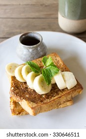 French Toast with Bananas French Toast served with fresh bananas and honey on handmade porcelain plate.