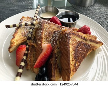French Toast Breakfast with strawberries, blueberries, chocolate straws, coconut and maple syrup