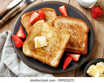 French toast with butter and honey on dark plate, top view