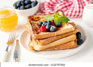 French toast with fresh blueberries, raspberries and honey on white plate. Tasty breakfast