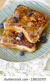 French toast with powdered sugar and maple syrup.