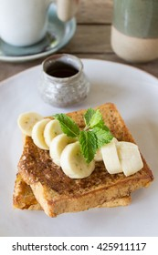 French Toast served with fresh bananas and honey served on handmade porcelain plate. Mint leaf as a decoration.