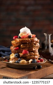 French toast stacked high and topped with strawberries, blueberries, bananas, whip cream and maple syrup in a warm, rustic, inviting restaurant atmosphere.