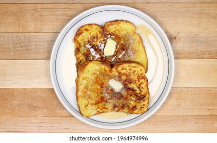 French Toast, two slices on a small plate, melted butter, syrup and cinnamon, overhead, straight down, butcher block background.
