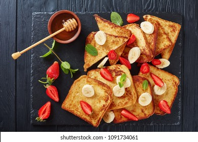 French toasts with appetizing, lacy brown crust and fluffy inside served on a black slate tray with strawberries, banana slices, mint and honey, view from above