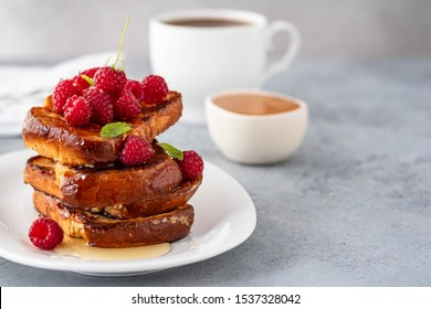 French toasts, French toasts made of sliced brioche with fresh raspberries, honey and mint. Delicious breakfast or dessert