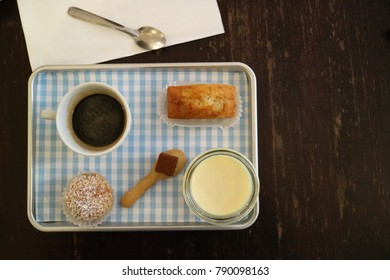 French traditional café gourmand, it's a coffee with small pieces of variety desserts in plate on a wooden table