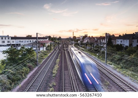 A french train speeds off into the sunset.