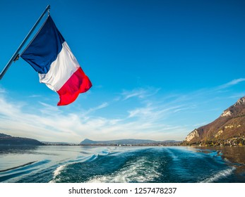 French Tricolore as seen from the stern of a boat on Lake Annecy, Europe's cleanest lake, Annecy, Haute-Savoie, France, Europe