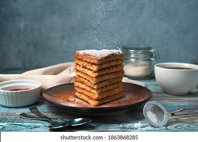 French waffle cake on a blue-gray background. The concept of desserts. Side view.