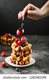 French waffles for breakfast. Women hand pours syrup from the spoon for dessert. Beautiful serve waffer cake with berries