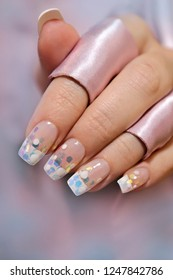 French wedding manicure with translucent glitters, white dots close-up. Nail art.