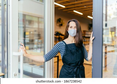 Französische Frau in Schutzmaske offene Tür des Ladens für den Empfang der Kunden in der Kaffeehaus, kleine Unternehmer und Start-up mit Cafe-Shop, Installation von offenen und geschlossenen Konzept