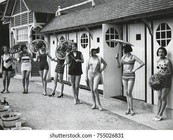 French women pose in the latest fashionable bathing suits outside their beach cabanas at Dieppe. Ca. 1925.