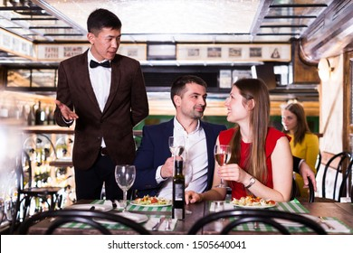 Frendly administrator is interested in the couple about quality of service in restaurant.