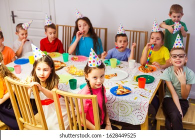 Frendly children celebrating birthday together. Kids eating pizza and enjoying party