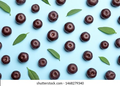 Fresh acai berries with leaves on blue background, flat lay