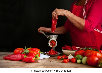 Fresh Ajvar made of tomatoes and paprika on the rustic wooden table. Ajvar with woman hand.
