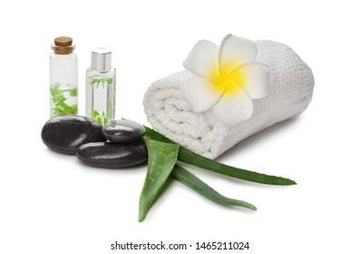 Fresh aloe leaves with essential oil, spa stones and towel on white background