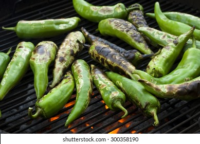 Fresh anaheim chili peppers roasting over a charcoal fire