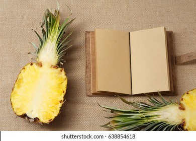 Fresh Ananas and Notebook lying on a sackcloth surface