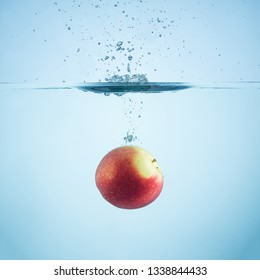 Fresh apple dropped in water with splash.