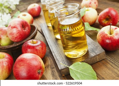 Fresh apple juice in the bottle on the wooden table
