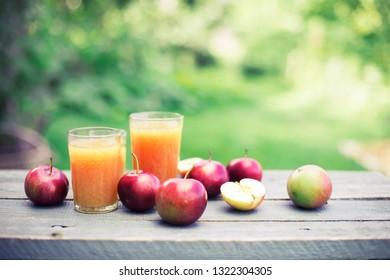 FRESH apple juice over summer nature background