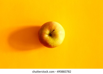 Fresh apple in the middle on a yellow background