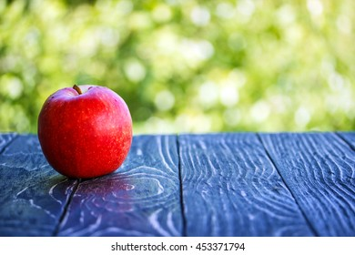 fresh apple on wooden table outdoors in the garden