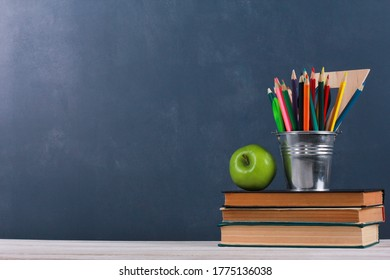 Fresh apple and pencils pot on stacked books, school supplies on white desk with dark blue wall in background. Side view, copy space, close-up. Learning, education concept - Shutterstock ID 1775136038