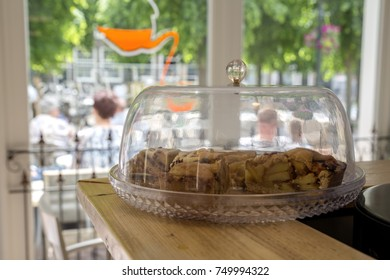 Fresh apple pie under a glass bell on a wooden counter in a shop.