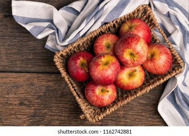 Fresh apples in basket on wood table