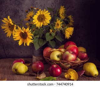 Fresh apples in basket with sunflowers on wooden table.