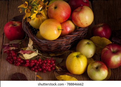 Fresh apples in basket with wiburnum on wooden table