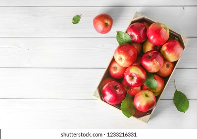 Fresh apples from beautiful garden. Apple in wooden box on white table top view and copy space.