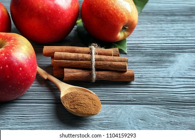 Fresh apples with cinnamon sticks and powder on wooden table