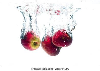 Fresh apples fruits falling in water splash, isolated on white background