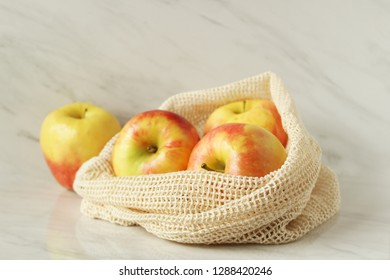Fresh apples in reusable produce bag. Plastic free concept. Copy space.