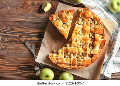 Fresh apples with tasty homemade pie on wooden table