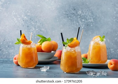 Fresh apricot cocktail with ice and mint on the blue background. Selective focus image. Bar concept and summer drinks concept