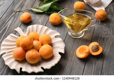 Fresh apricots and gravy-boat of oil on wooden table