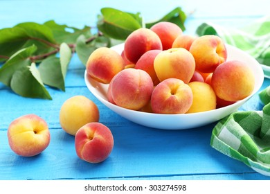 Fresh apricots in plate on a blue wooden background