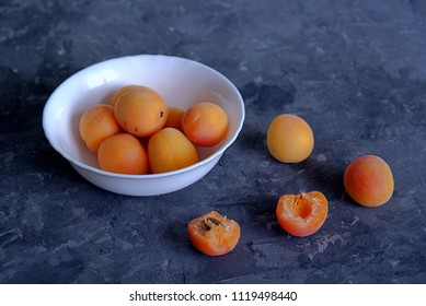 Fresh apricots in a white bowl on a dark gray concrete background